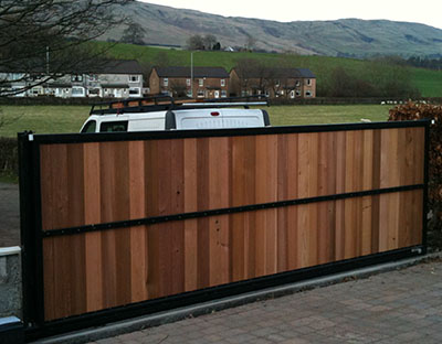 Wooden Sliding gate on rail with automated access.